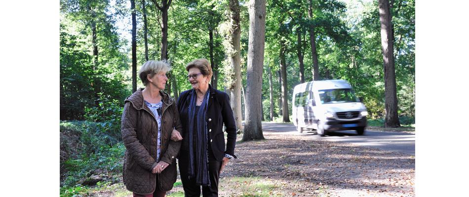 Twee dames in het bos bij een Deeltaxi busje