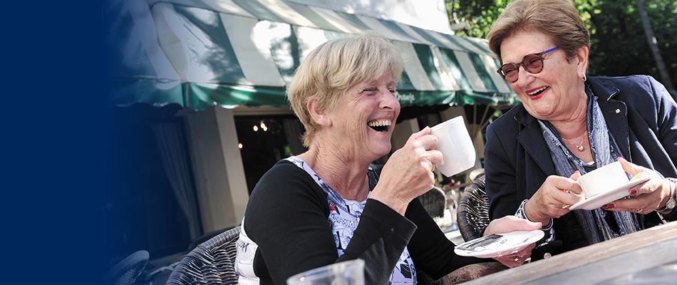 Twee lachende dames drinken samen een kopje koffie