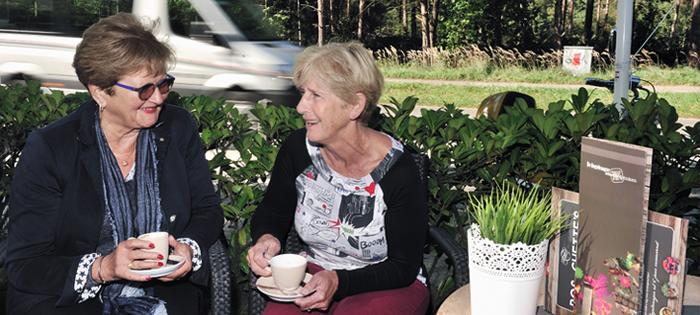 Twee dames in gesprek zittend voor Deeltaxi busje